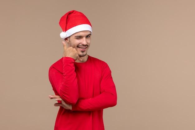 Widok z przodu młody mężczyzna z uśmiechem na twarzy na brązowym tle świątecznych emocji