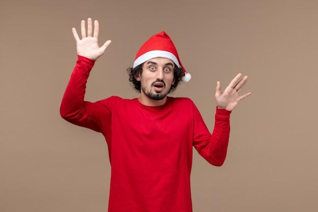 Widok z przodu młody mężczyzna z zaskoczoną twarzą na brązowym tle emocji świąt bożego narodzenia