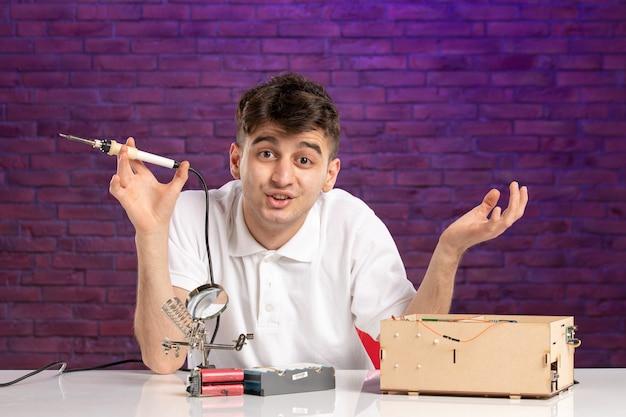 Widok z przodu młody mężczyzna za biurkiem próbuje naprawić mały układ konstrukcyjny na fioletowej ścianie