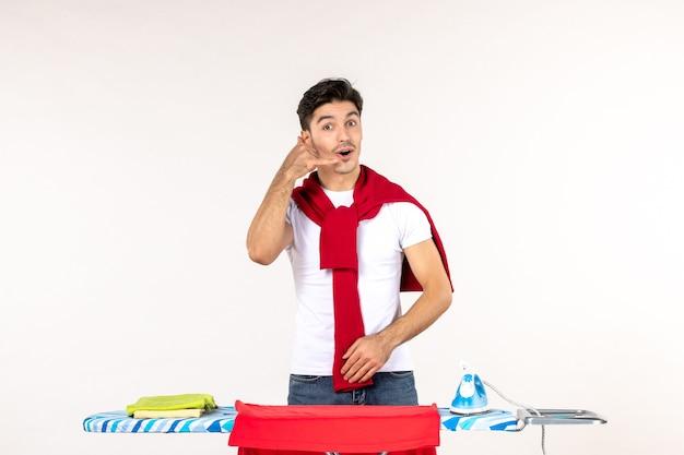 Widok z przodu młody mężczyzna za deską do prasowania z prośbą o telefon na białej ścianie człowiek praca domowa czysty wysiłek emocje prace domowe moda ubrania