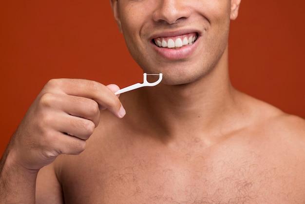 Widok z przodu młody mężczyzna za pomocą nici dentystycznej