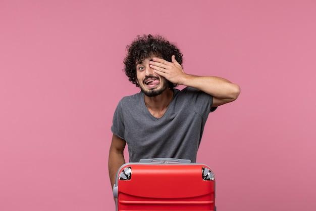 Widok z przodu młody mężczyzna zakrywający połowę twarzy na różowej przestrzeni