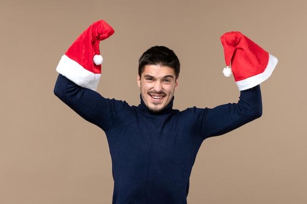 Widok z przodu młody mężczyzna zginanie z czerwonymi czapkami na brązowym tle emocji świąt bożego narodzenia