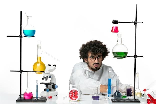 Widok z przodu młody naukowiec mężczyzna w białym specjalnym garniturze pracujący z rozwiązaniami