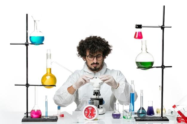 Widok z przodu młody naukowiec mężczyzna w białym specjalnym garniturze próbuje naprawić mikroskop