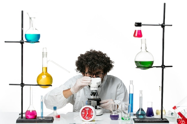 Widok z przodu młody naukowiec mężczyzna w białym specjalnym garniturze próbuje użyć mikroskopu