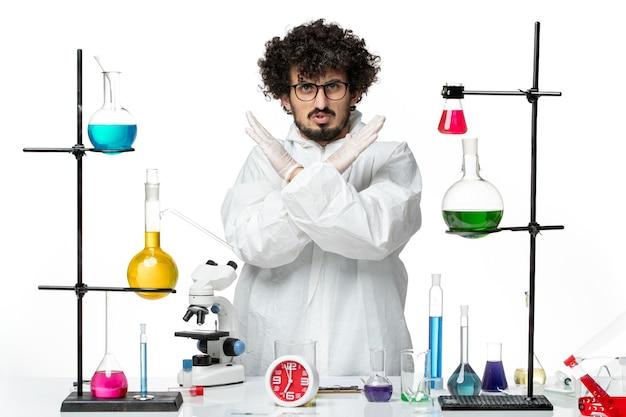 Widok z przodu młody naukowiec mężczyzna w białym specjalnym garniturze przedstawiający znak zakazu na białej ścianie science covid lab pandemic chemistry