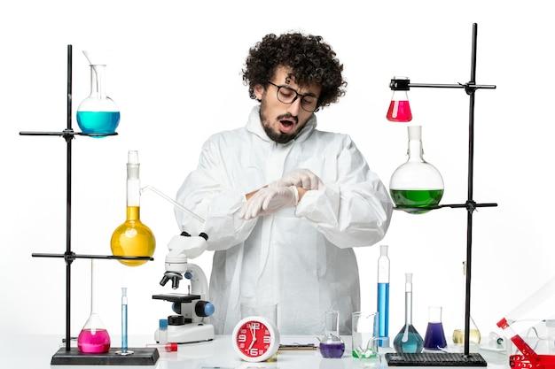 Widok z przodu młody naukowiec mężczyzna w białym specjalnym garniturze stojący wokół stołu z rozwiązaniami patrząc na jego nadgarstek