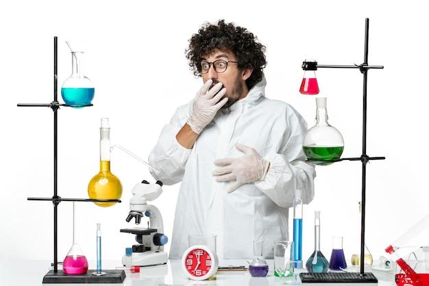 Widok z przodu młody naukowiec mężczyzna w białym specjalnym garniturze stojący wokół stołu z rozwiązaniami
