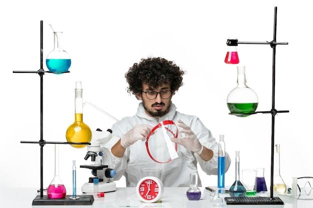 Widok z przodu młody naukowiec mężczyzna w białym specjalnym garniturze trzyma coś