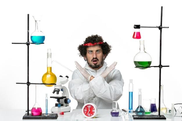 Widok z przodu młody naukowiec mężczyzna w specjalnym garniturze i hełmie ochronnym na białym biurku laboratorium naukowe covid męskiej chemii