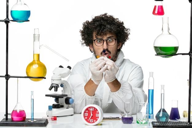 Widok z przodu młody naukowiec mężczyzna w specjalnym garniturze, pracujący przy stole z rozwiązaniami na białej ścianie