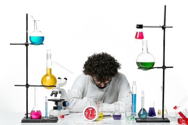 Widok z przodu młody naukowiec mężczyzna w specjalnym garniturze siedzi z roztworami na białej ścianie