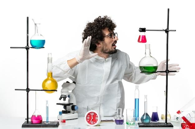 Widok z przodu młody naukowiec mężczyzna w specjalnym garniturze stojący wokół stołu z rozwiązaniami na białej ścianie
