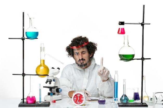 Widok z przodu młody naukowiec mężczyzna w specjalnym garniturze z hełmem ochronnym, piszący notatki na białej ścianie laboratorium naukowego covid chemistry male