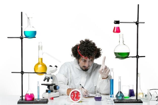 Widok z przodu młody naukowiec mężczyzna w specjalnym garniturze z hełmem ochronnym, piszący notatki na białym biurku laboratorium naukowego covid chemistry male