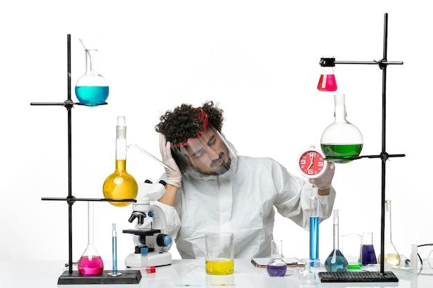 Widok z przodu młody naukowiec mężczyzna w specjalnym garniturze z hełmem ochronnym trzymający zegar na jasnobiałej ścianie