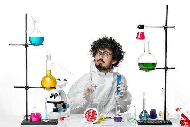 Widok z przodu młody naukowiec płci męskiej w specjalnym garniturze, trzymając kolbę z roztworem na jasnobiałej ścianie