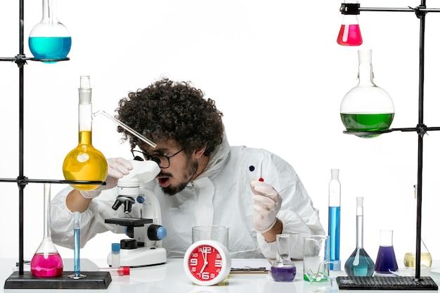 Widok z przodu młody naukowiec płci męskiej w specjalnym garniturze, trzymając próbki i używając mikroskopu na białej ścianie