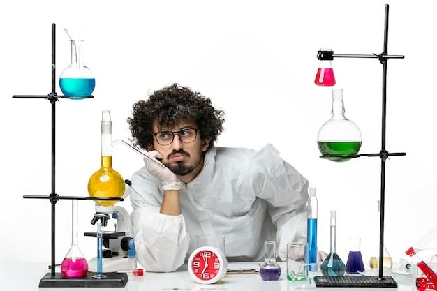 Widok z przodu młody naukowiec w białym specjalnym garniturze, siedzący przy stole z roztworami na białej ścianie science covid pandemic chemistry lab