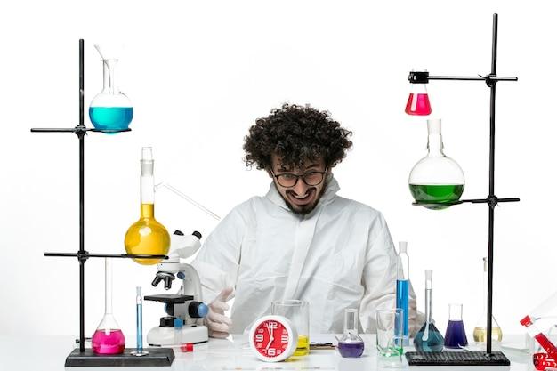 Widok z przodu młody naukowiec w specjalnym garniturze, siedzący z rozwiązaniami na jasnobiałej ścianie