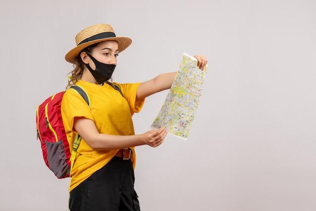 Widok z przodu młody podróżnik z czerwonym plecakiem patrzący na mapę