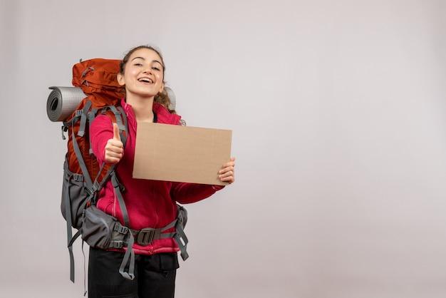 Widok z przodu młody podróżnik z dużym plecakiem trzymającym karton z kciukami do góry