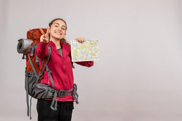 Widok z przodu młody podróżnik z dużym plecakiem trzymającym mapę, robiący znak ok