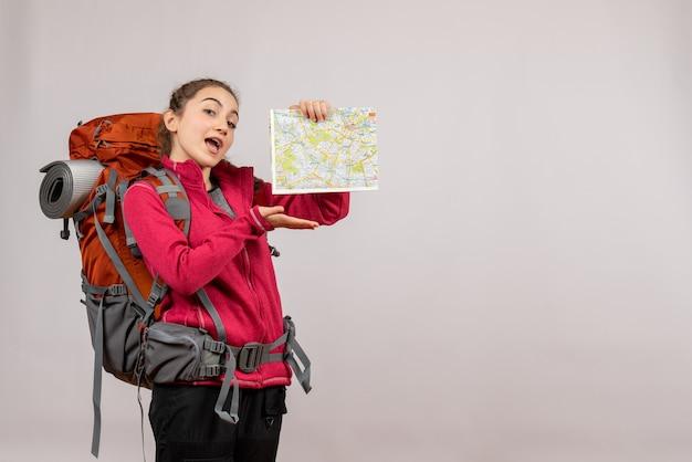 Widok z przodu młody podróżnik z dużym plecakiem wskazującym na mapę
