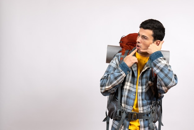 Widok z przodu młody podróżnik z plecakiem, dzwoniąc do mnie gestem telefonu