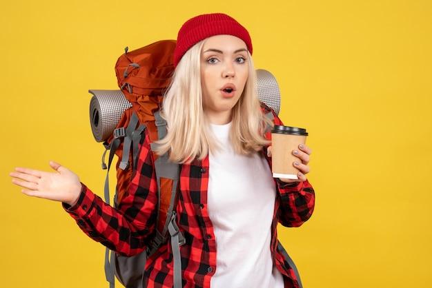 Widok z przodu młody podróżnik z plecakiem trzymając kubek kawy stojący na żółtej ścianie