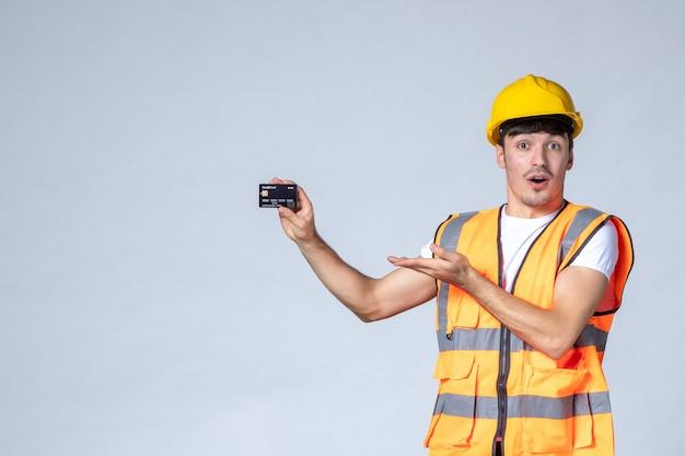 Widok z przodu młody pracownik płci męskiej z czarną kartą bankową na białym tle