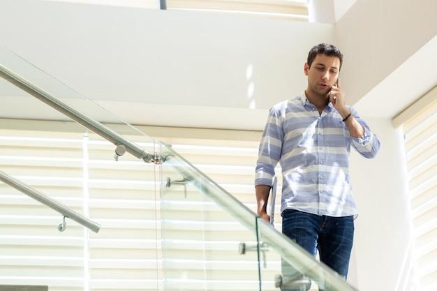 Widok z przodu młody przystojny mężczyzna w pasiastej koszuli rozmawia i omawia kwestie pracy przez telefon podczas budowania aktywności w ciągu dnia