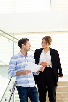 Widok z przodu młody przystojny mężczyzna w pasiastej koszuli rozmawia i omawia kwestie pracy z młodą bizneswoman podczas budowania aktywności w ciągu dnia