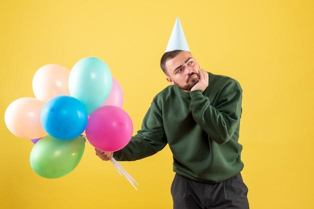 Widok z przodu młody samiec z kolorowymi balonami na żółto