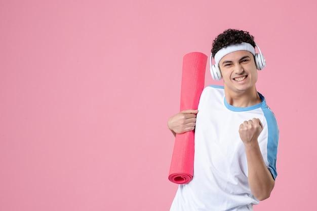 Widok z przodu młody sportowiec płci męskiej w ubraniach sportowych na różowej ścianie