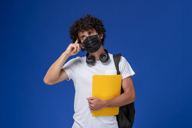 Widok z przodu młody student w białej koszulce na sobie czarną maskę i trzymający żółte pliki myśląc na jasnoniebieskim tle.