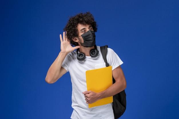 Widok z przodu młody student w białej koszulce, ubrany w czarną maskę i trzymający żółte pliki, próbujący usłyszeć na jasnoniebieskim biurku.
