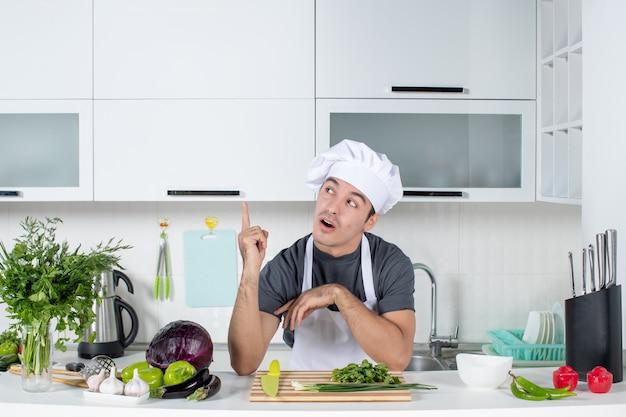 Widok z przodu młody szef kuchni w mundurze w kuchni