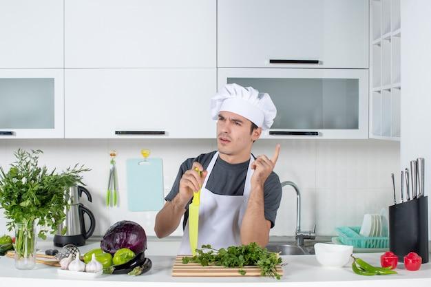 Widok z przodu młody szef kuchni w zamieszaniu trzymający nóż
