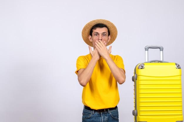 Widok z przodu młody turysta stojący w pobliżu żółtej walizki kładąc ręce na ustach