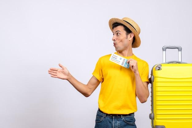 Widok z przodu młody turysta stojący w pobliżu żółtej walizki, patrząc na coś z wielkim zainteresowaniem