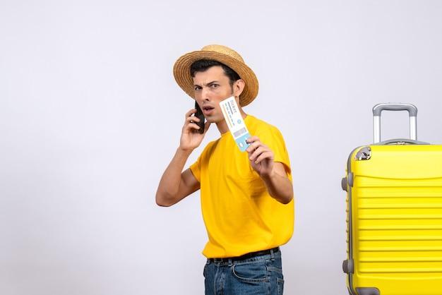 Widok z przodu młody turysta stojący w pobliżu żółtej walizki rozmawiający przez telefon trzymając bilet lotniczy