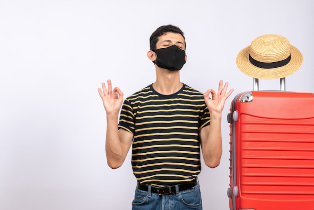 Widok z przodu młody turysta z czarną maską stojący w pobliżu czerwonej walizki, gestykulujący w porządku