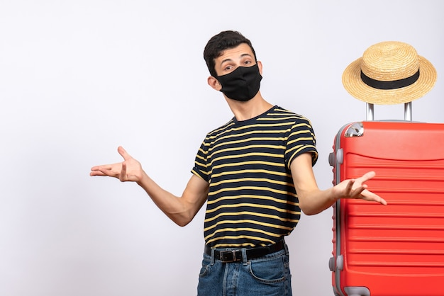 Widok z przodu młody turysta z czarną maską stojący w pobliżu czerwonej walizki, otwierając ręce