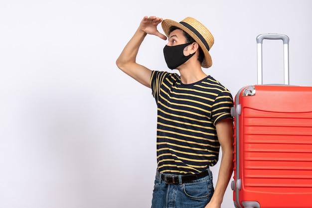 Widok z przodu młody turysta z czarną maską stojący w pobliżu obserwowania czerwonej walizki