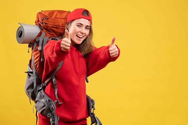Widok z przodu młody turysta z plecakiem i czerwoną czapką skierowaną w górę