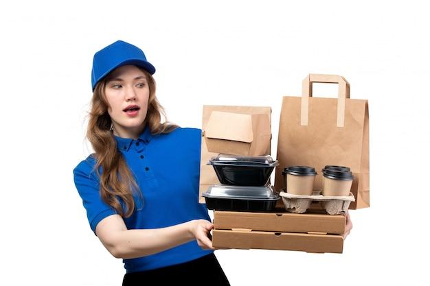 Widok z przodu młody żeński kurier żeński pracownik usług dostawy żywności gospodarstwa dostawy żywności i pudełka na białym tle