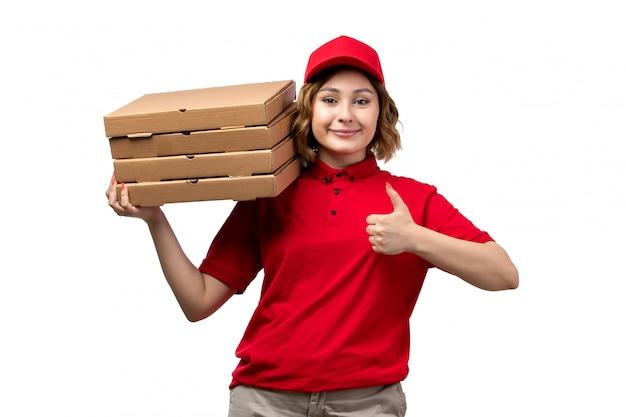 Widok z przodu młody żeński kurier żeński pracownik usług dostawy żywności posiadający pakiety dostawy żywności uśmiecha się na białym tle