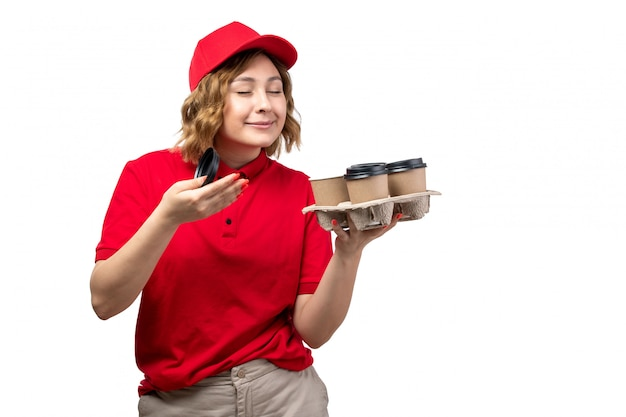 Widok z przodu młody żeński kurier żeński pracownik usług dostawy żywności trzymając filiżanki kawy pachnące na białym tle